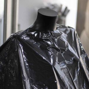 detalle capas de corte desechables en material plástico para peluquería y barbería negras